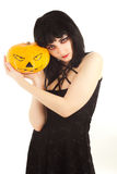 Woman in black dress holding a Jack-o'-lantern Royalty Free Stock Image