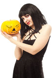Woman in black dress holding a Jack-o'-lantern Royalty Free Stock Photos