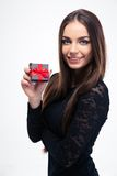 Woman in black dress holding jewerly gift box. Smiling young woman in black dress holding jewerly gift box isolated on a white background and looking at camera royalty free stock images