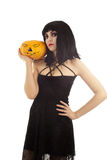 Woman in black dress holding a pumpkin. Isolated on white Stock Image