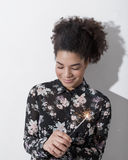 Woman in black dress holding sparkler. Against white wall Stock Images
