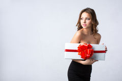 Woman in a black dress holding a white box with a red bow and ribbon. Royalty Free Stock Photography