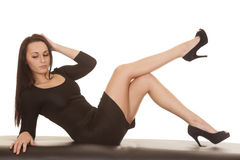 Woman black dress lay back leg up Royalty Free Stock Photos