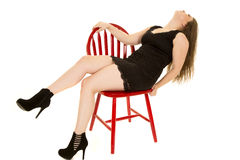 Woman black dress lean back red chair Stock Photos