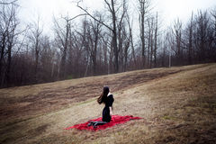 Woman in black dress and long hair sitting on red carpet in cold forest Stock Images