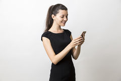 Woman in black dress is looking at her cell phone screen Royalty Free Stock Images