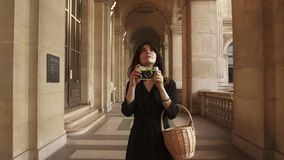 Woman in black dress making a photo walking outside Louvre museum. Smiling woman in black dress walking holding a wicker basket and a film camera making a photo stock video footage