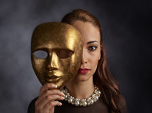 Woman in a black dress with a pearl necklace and old mask Royalty Free Stock Images