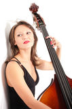 Woman in black dress play double bass by white wall Stock Photo