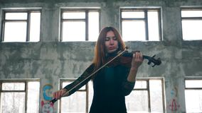 A woman in a black dress is playing the violin. 4K stock video