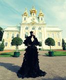 Woman in black dress posing next to the palace. Stock Image