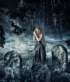Woman in black dress praying on cemetery Royalty Free Stock Images