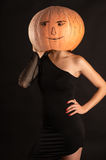 Woman in a black dress with a pumpkin on head Stock Photos