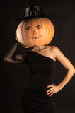 Woman in a black dress with a pumpkin on head Royalty Free Stock Photo