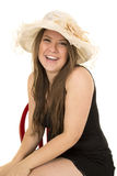 Woman black dress red chair hat hands knees happy Royalty Free Stock Image