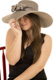 Woman black dress red chair hat peek under hat Stock Images