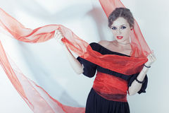 Woman in black dress with red sash Stock Image
