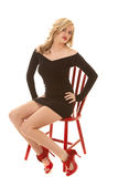 Woman in black dress and red shoes on red chair Royalty Free Stock Image