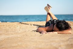 Woman in black dress relaxing on beach Stock Photos