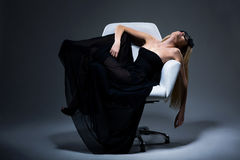 Harmony & Sensuality. Romantic Blond Female in Black Dress resting in Armchair. Satisfaction Royalty Free Stock Photography