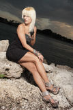 Woman in a black dress on the rocks Royalty Free Stock Photos