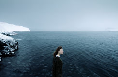 Woman in Black Dress at the Sea Near the Ice Mountain Under Gray Sky Royalty Free Stock Images
