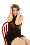 Woman black dress sit on chair hands hair Royalty Free Stock Photography