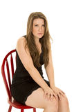 Woman black dress sit on chair hands on knees Stock Images