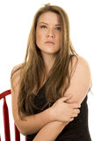 Woman black dress sit on red chair touch arm Royalty Free Stock Image