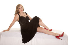 Woman in black dress sit side red shoes Royalty Free Stock Photography