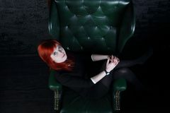 Woman in black dress sits in leather armchair. And looks up in black studio, top view Stock Image