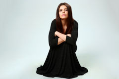 Woman in black dress sitting on the floor Stock Images