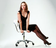 Woman in black dress sitting on the office chair Royalty Free Stock Images