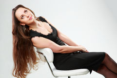 Woman in black dress sitting on the office chair Royalty Free Stock Photos