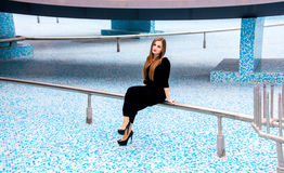 Woman in black dress sitting on pipe of empty fountain Royalty Free Stock Images