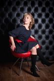 Woman in black dress sitting on a red chair Royalty Free Stock Photo