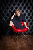 Woman in black dress sitting on a red chair Stock Photos
