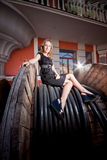 Woman in black dress sitting on top of huge bobbin Royalty Free Stock Photography