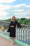 A woman in a black dress standing on the bridge Stock Photography