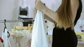 Woman in black dress standing next to rack with hangers indoors. Blonde choose clothes in light room. Lady in dark nightie hanging white lingerie on hanger stock video footage
