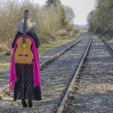 Woman with black dress standing on the train tracks with a pink shawl, a brown hat and a guitar on her back royalty free stock image