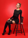 Woman in a black dress and stockings sitting on the chair Stock Photography