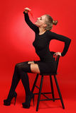 Woman in a black dress and stockings sitting on the chair Royalty Free Stock Photography