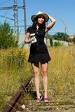 The woman stands on overgrown tracks, holds a glass full of money in her hand and waits for a train. A woman in a black dress with straw hat stands on the rails royalty free stock photo