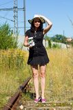 The woman stands on overgrown tracks, holds a glass full of money in her hand and waits for a train. A woman in a black dress with straw hat stands on the rails royalty free stock image