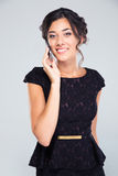 Woman in black dress talking on the phone Stock Image