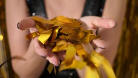 Woman in a black dress throws gold confetti. On a background of yellow tinsel stock footage