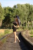 Woman in black dress with umbrella on rails Royalty Free Stock Photos