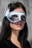 Woman in black dress wearing carnival mask Stock Image