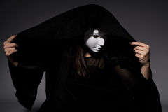 Woman in black dress and white mask Stock Photos